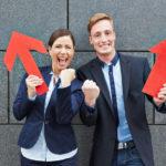 Zwei erfolgreiche Geschäftsleute jubeln und halten zwei rote Pfeile