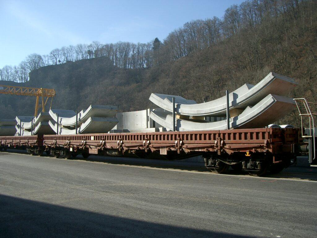 Ein Flachwagen beladen mit Tübbinge steht auf einem Anschlussgleis.